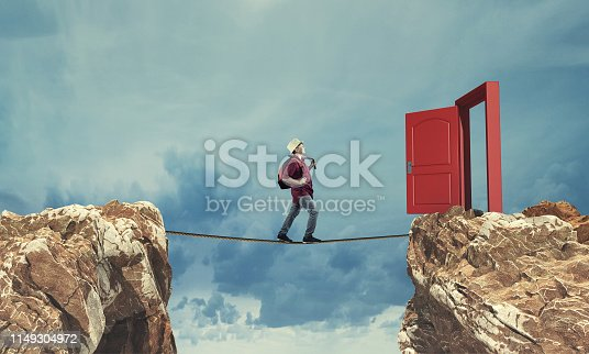 Surreal challenge overcome . Young man conquering obstacle balancing on slackline rope above a gap  between two mountain peaks.Risk taking , success concept.
