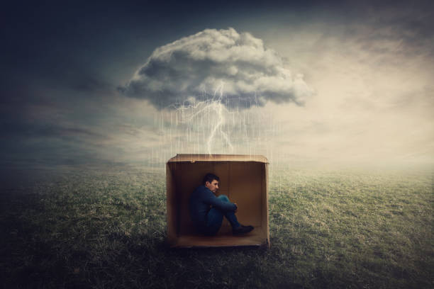 surreal concept with a scared guy shelters inside a cardboard box. introvert man caged by own fears as a thunderstorm cloud trapped him under the rain. mysterious storm as emotional crisis symbol. - trap house stock pictures, royalty-free photos & images