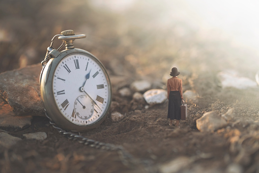 surreal image of a giant clock and a small business traveler woman