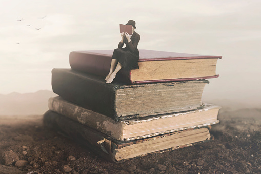 istock Surreal image of a woman reading sitting on top of a book 983425976
