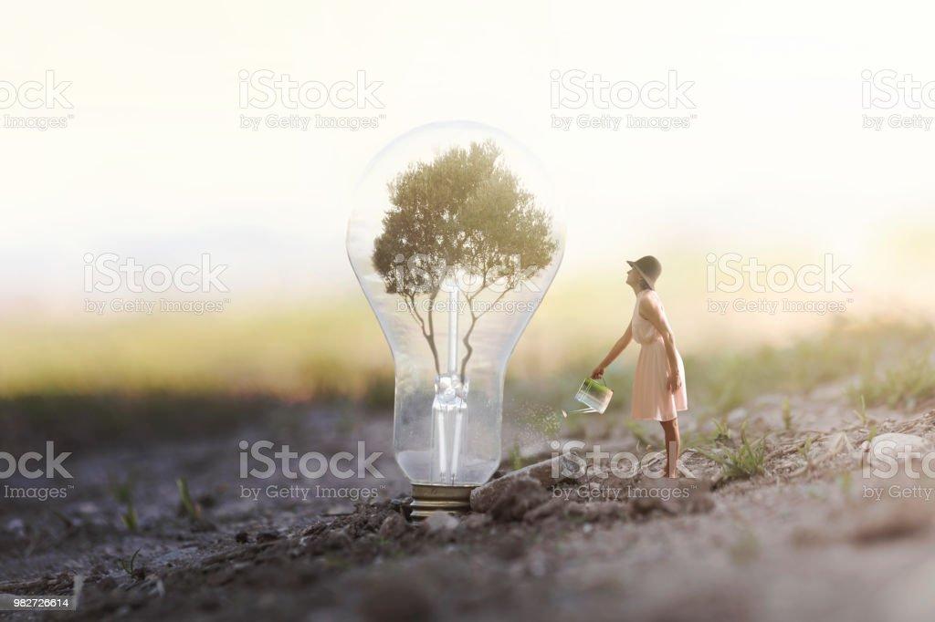imagen surrealista de una mujer de regar su planta que necesita energía a una bombilla de luz - foto de stock
