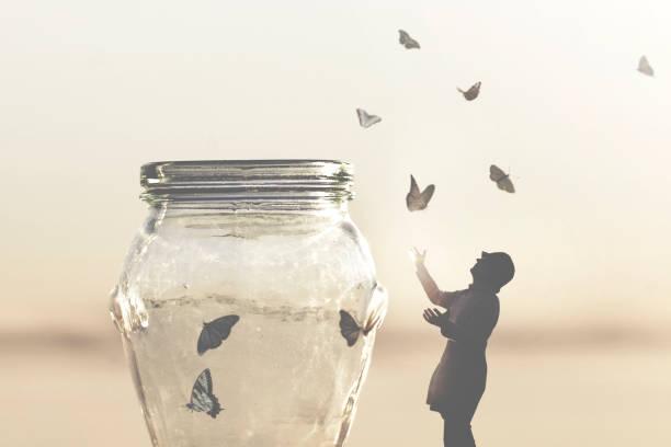 Surreales Bild einer Frau, die Schmetterlingen in einer Vase die Freiheit gibt – Foto