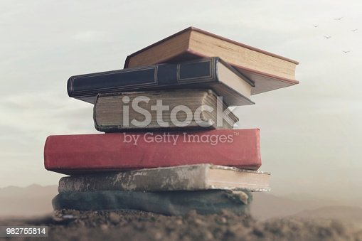 istock Surreal image of giant books on top of each other touching the sky 982755814