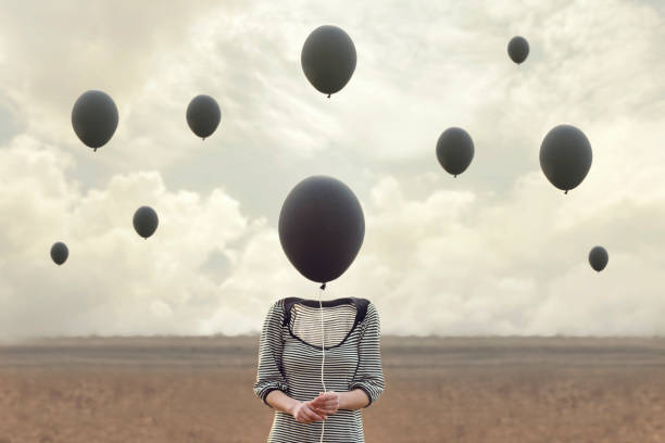 surreal image of woman and blacks balloons flying - enigma images stock photos and pictures