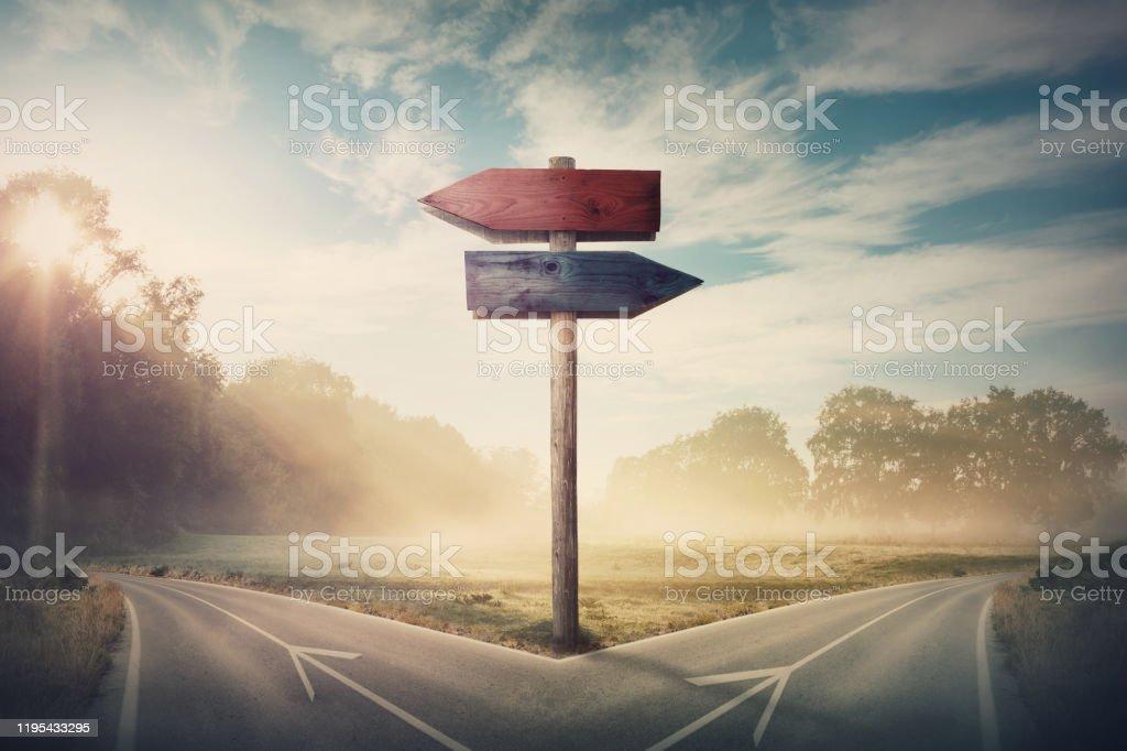 Surreale Landschaft mit einer geteilten Straße und Wegweiser Pfeile zeigt zwei verschiedene Kurse, linke und rechte Richtung zu wählen. Die Straße teilt sich in unterschiedliche Richtung. Schwierige Entscheidung, Wahlkonzept. - Lizenzfrei Wahlmöglichkeit Stock-Foto