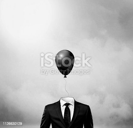 861862204 istock photo Surreal man with big black balloon suspended over his head 1126630129