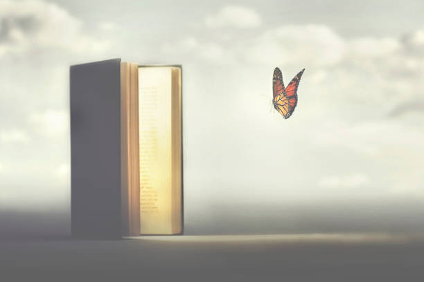 surreal moment of a butterfly entering the pages of a book stock photo