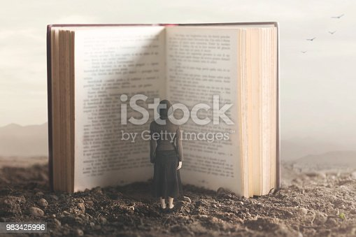 istock surreal moment of a small woman reading a giant book in a desert land 983425996