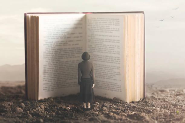 사막 땅에서 거 대 한 책을 읽고 작은 여자의 초현실적인 순간 - 역사 뉴스 사진 이미지