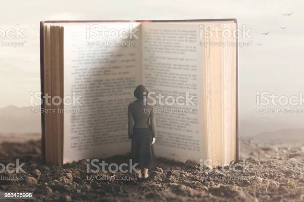 Photo of surreal moment of a small woman reading a giant book in a desert land