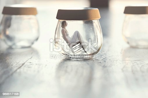 istock surreal moment of a tiny woman sitting on a chair inside a glass vase in the table at home 988517168