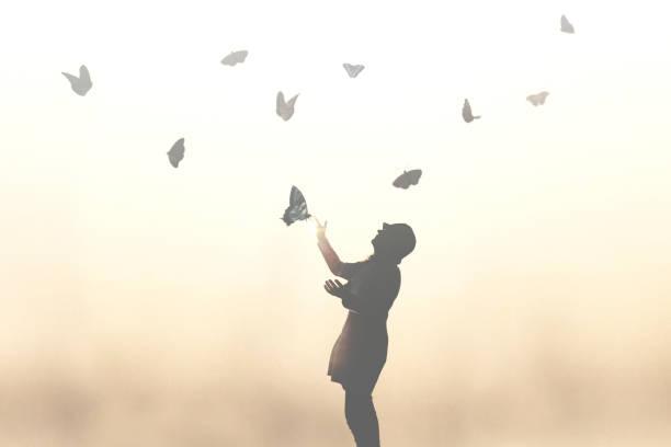 Surrealer Moment einer Frau, die mit Schmetterlingen tanzt – Foto
