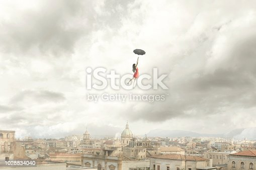 istock Surreal moment of a woman flying with her umbrella over the city 1028834040