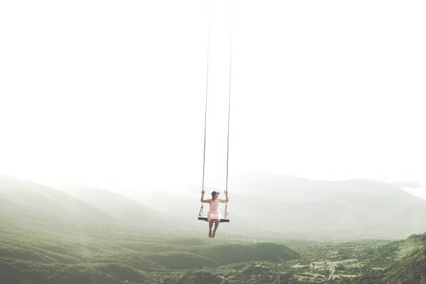 surreal moment of a woman having fun on a swing hanging from the sky stock photo