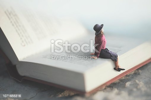 istock surreal moment of a woman relaxes sitting on a giant book 1071655316