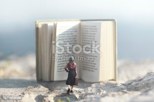 istock surreal moment of a woman walking towards a giant book 1071659386