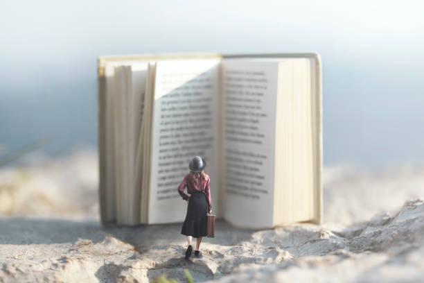 surreale Moment einer Frau zu Fuß in Richtung ein riesiges Buch – Foto