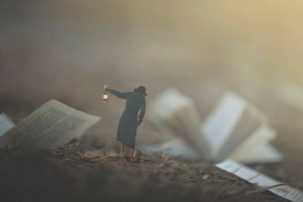 surreal moment of a woman with lantern walking confused in the fog between pages and books stock photo