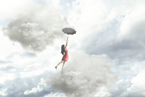 Surreal moment of an elegant woman flying in the middle of the clouds hanging on her umbrella stock photo