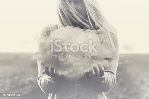 861862204 istock photo Surreal moment, solitary woman holding in her hands a gray cloud 1070935144