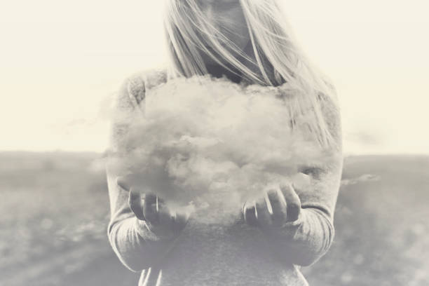 Surreal moment, solitary woman holding in her hands a gray cloud stock photo
