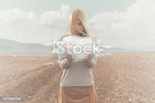istock surreal moment , woman holding in her hands a soft cloud 1070932094