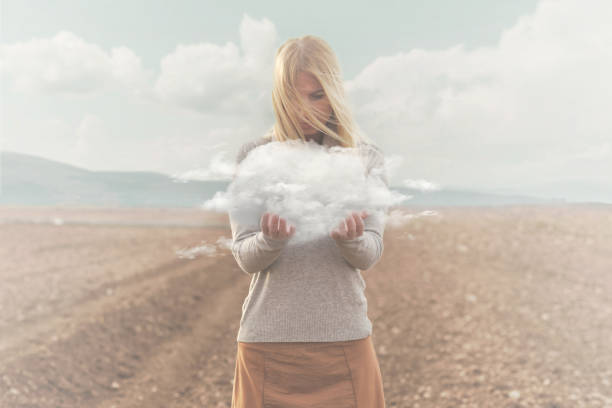 surreal moment , woman holding in her hands a soft cloud stock photo