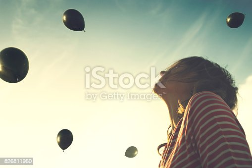 istock Surreal moment, woman looks surprised with a rain of black balloons falling from the sky 826811960
