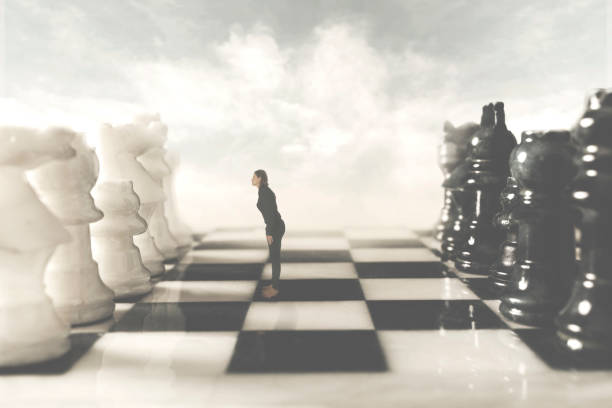 surreal photo of a black woman who challenges her white rival in the chessboard stock photo