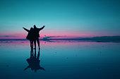 Surreal pop art style silhouette of couple raising arms enjoy the mirror effect of Uyuni Salt Flats, Bolivia, South America, (Self Portrait)