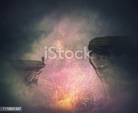 Surreal scene as a fearless man stand on the edge of a cliff watching the magical fire sparkles eruption as from a volcano crater. Problem to overcome the gap, mysterious quest, conquering concept.