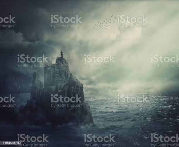 Photo of Surreal scene as man silhouette standing on the top of a cliff surrounded by the sea water. Meditation metaphor, conquering adversity and overcoming challenges concept.