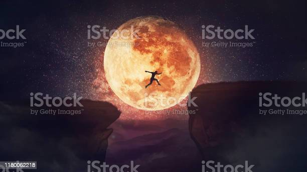 Photo of Surreal scene, self overcome concept, as determined man jump over a chasm obstacle. Way to win and success over starry night with full moon background. Motivation for achieving goals.