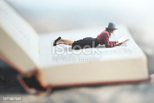 istock surreal situation of a woman reading her book lying on a giant book 1071657032