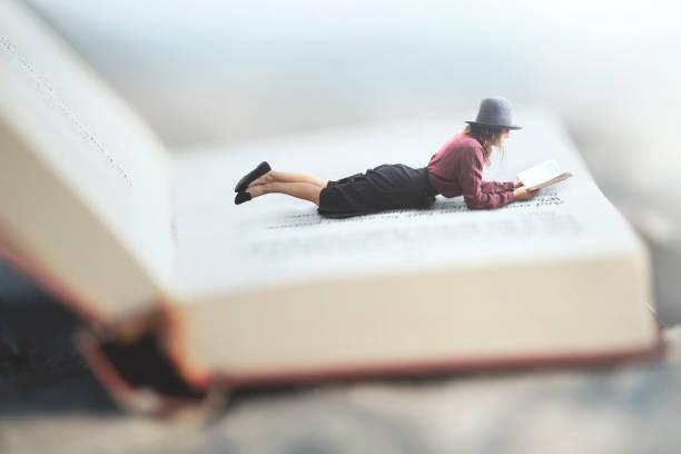 surreale Situation einer Frau, die ihr Buch auf ein riesiges Buch liegend – Foto