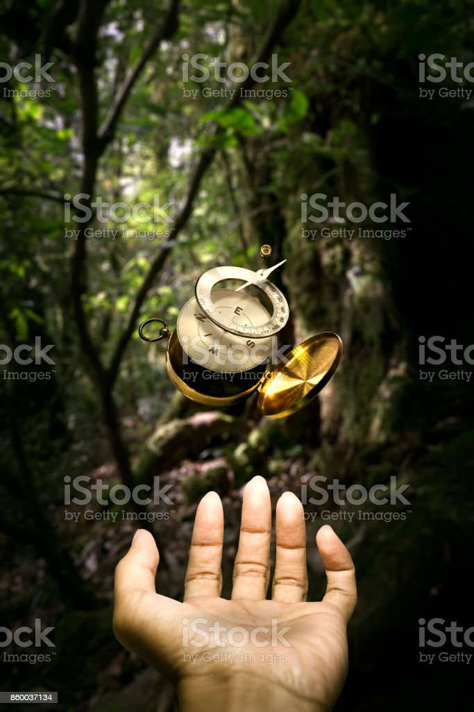 Surrealistic disintegrate compass floating over hand stock photo