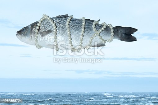 Surrealistic isolated fish with a pearl necklace floating in the sky above the sea, Magritte inspired