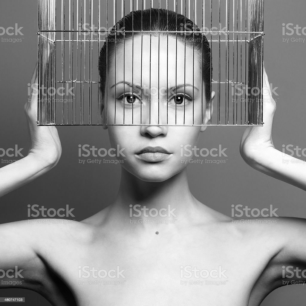 Surrealistic portrait of young lady with cage stock photo