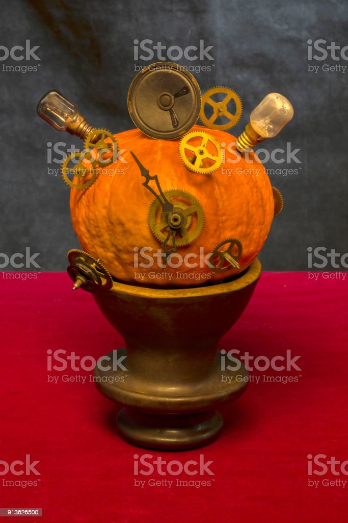 Surrealistic still life with pumpkin, gears and bulbs stock photo