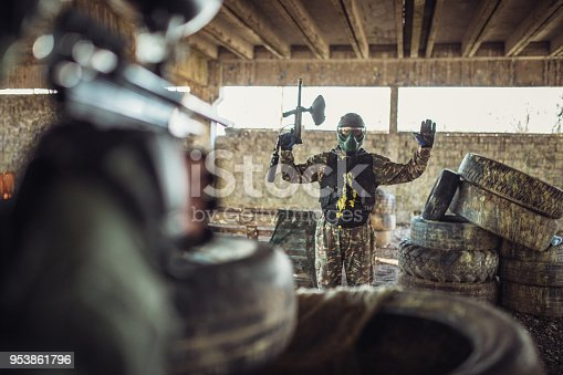 Group of people, playing paintball on a rural terrain in abandoned building, one of them got shot.