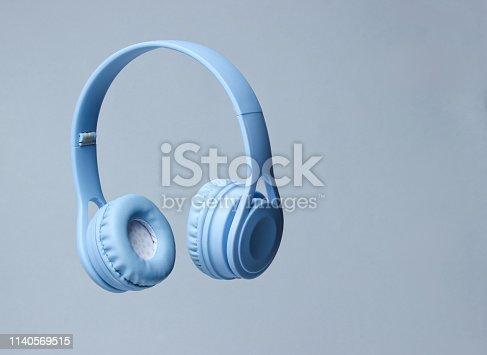 istock 3D surround photo blue wireless headphones on gray background. 1140569515