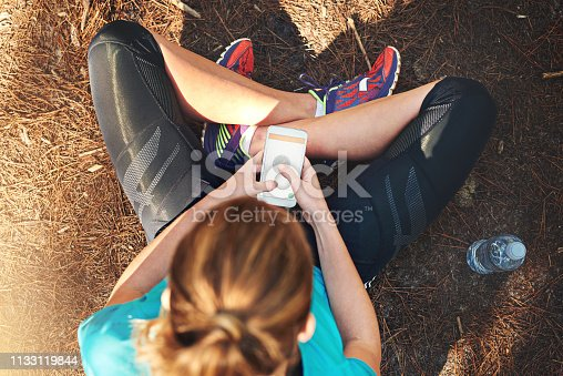 Shot of a sporty young woman using her cellphone while out in nature