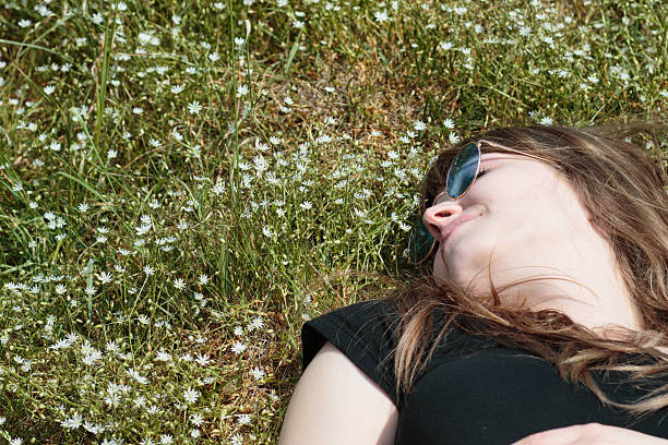 latvian flower girl asleep in stitchwort star field - whiteway latvian outdoor girl stock photos and pictures