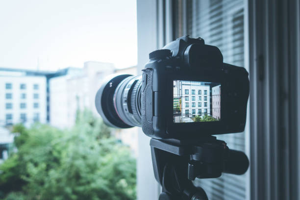 Surveillance and stalking concept: Camera with telephoto lens on tripod, observing a house Professional with telephoto lens on tripod, surveillance and stalking creepy stalker stock pictures, royalty-free photos & images