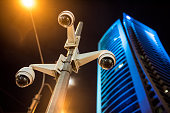 Three surveillance cameras on a pole in the city. City lights and office building in back.