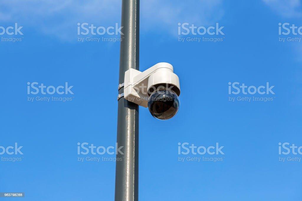 Rock Camera Surveillance : Surveillance cctv camera mounted on post against the blue sky stock
