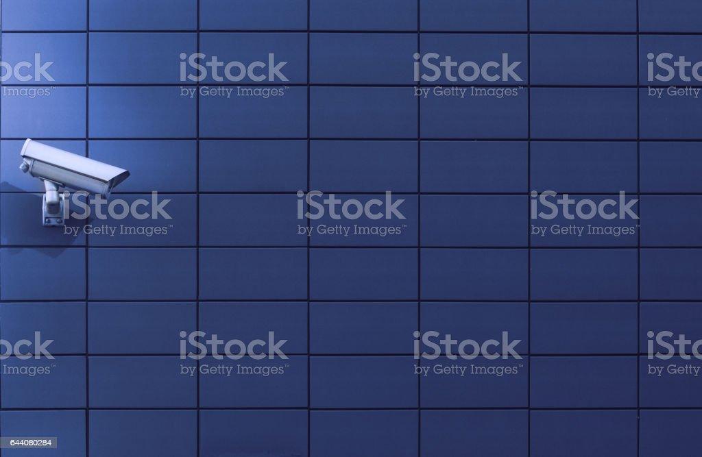 Surveillance monitoring camera against a blue wall stock photo