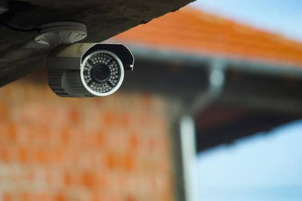 surveillance bewakingscamera onder de betonnen wand van het gebouw - bewakingscamera stockfoto's en -beelden