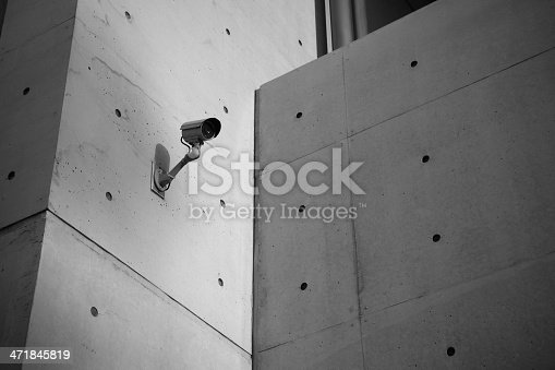 istock Surveillance Security Camera with concrete wall 471845819