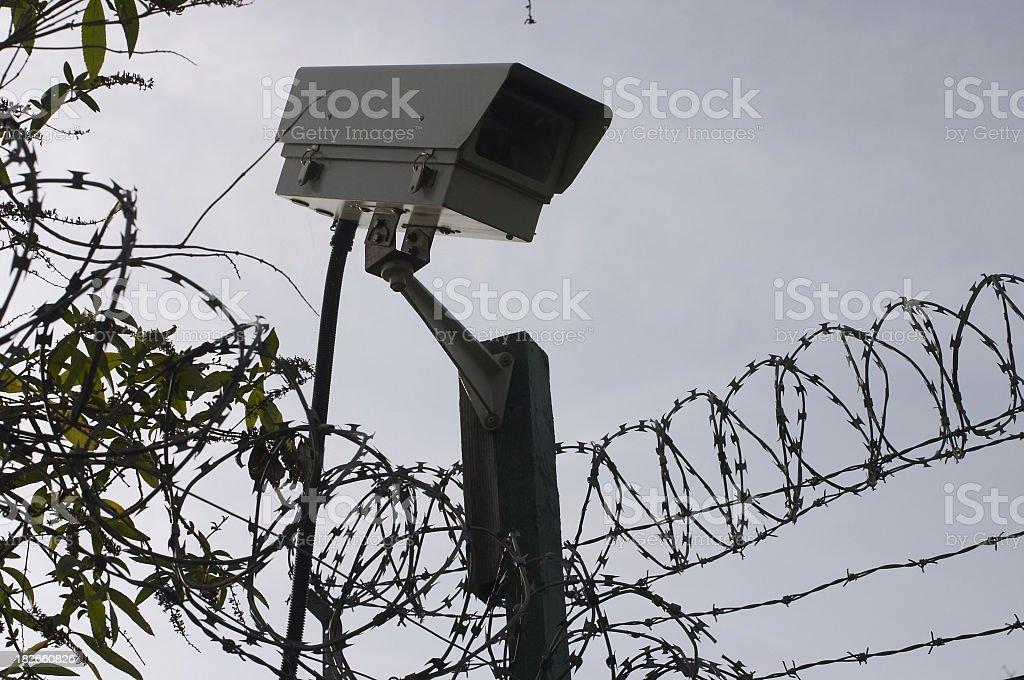 Surveillance video / spy camera and razor wire royalty-free stock photo